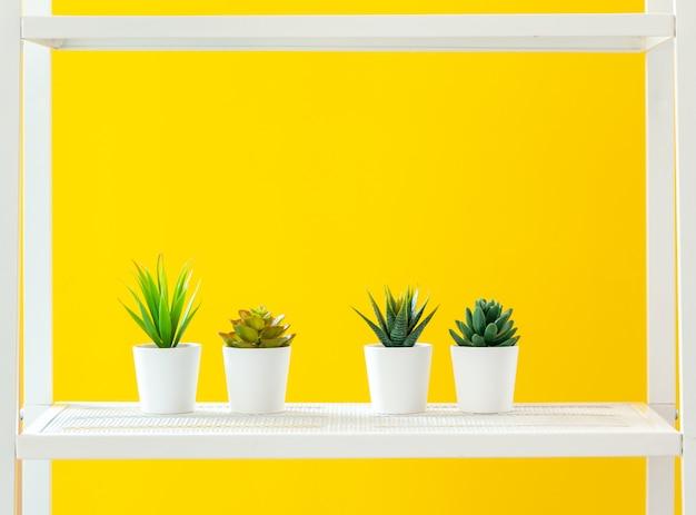 Étagère blanche avec des objets de papeterie contre un mur jaune vif