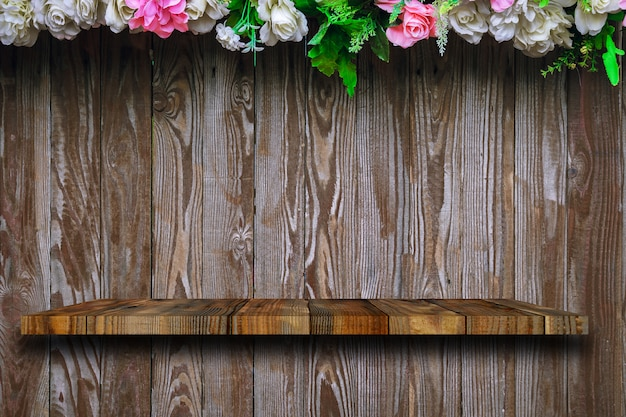 L'étagère en bois est sur les vieilles planches en bois avec des roses décorées sur le dessus.