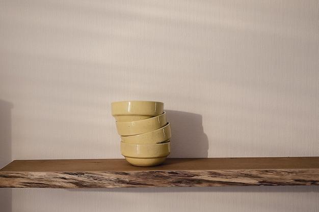 Étagère en bois flottante ouverte avec une pile de quatre assiettes en céramique faites à la main jaunes suspendues à un mur blanc dans un salon au design moderne. concept de maison minimaliste confortable.