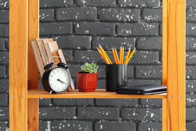 Étagère en bois avec des livres et des trucs contre le mur de briques noires