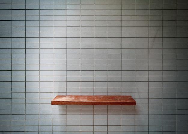 Étagère en bois vide sur le mur de carreaux.