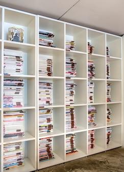 Étagère à livres blanche magnifiquement décorée, différents types de livres empilés