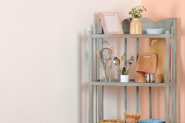 Étagère vintage avec vaisselle dans le coin de la pièce contre les murs blancs et pêche. étagère ancienne. intérieur