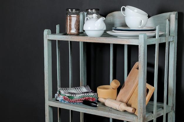 Étagère vintage avec vaisselle sur fond de mur noir. étagère ancienne. intérieur