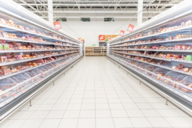 Étagères avec des aliments réfrigérés dans un supermarché. espace pour le texte. flou.
