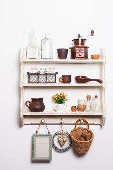 Étagères de cuisine blanches de style rustique avec ustensiles de cuisine sur le mur blanc