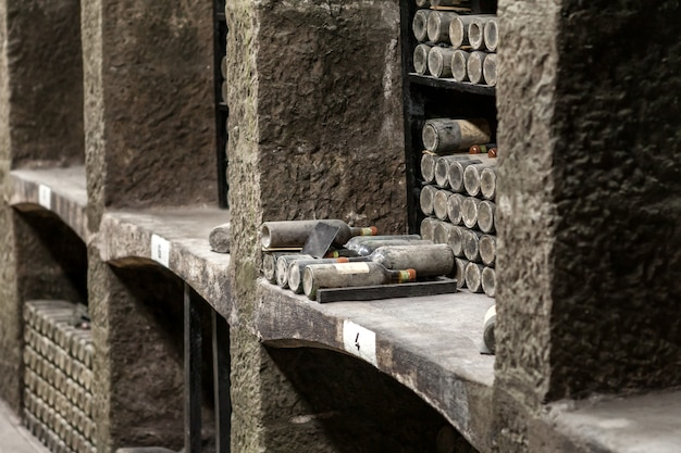 Étagères en pierre avec de coûteuses bouteilles de vin vintage couvertes de poussière