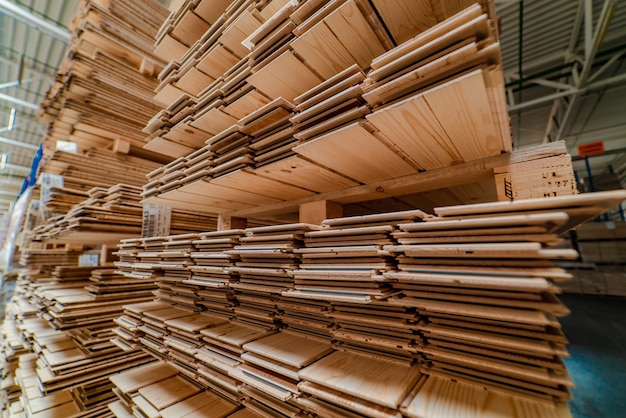 Des étagères avec une planche de parquet se trouvent dans l'entrepôt de l'usine.