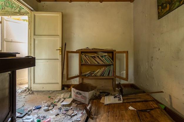 Étagères avec de vieux livres dans une maison abandonnée