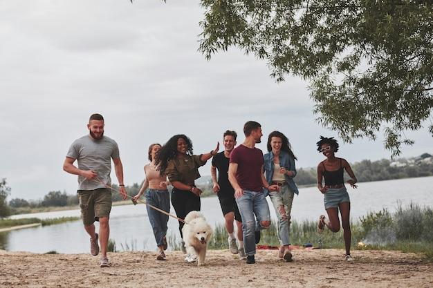 C'était une belle journée. un groupe d'amis multiethniques se promène avec un chien sur la plage.