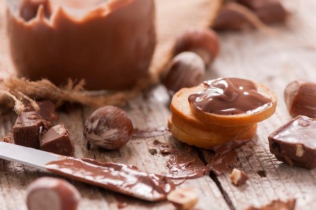 Étaler le chocolat et les noix sur une vieille planche à découper en bois