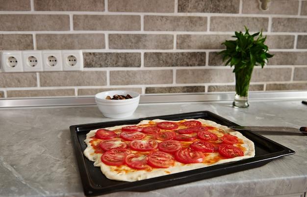 Étaler la pâte avec la sauce tomate et les tomates hachées sur une plaque à pâtisserie dans le comptoir de la cuisine.