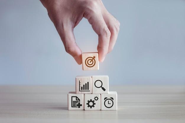 Étape de bloc de bois de pile de main d'homme sur la table avec la stratégie commerciale et le plan d'action d'icône