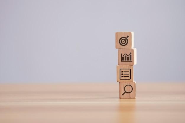Étape de bloc de bois sur la table avec la stratégie commerciale et le plan d'action d'icône