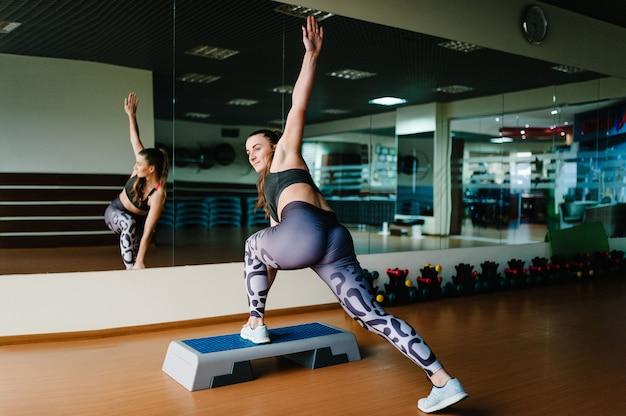 Étape plate-forme. vue arrière jeune belle femme sexy faisant des étirements et resserrement des fesses dans la salle de gym