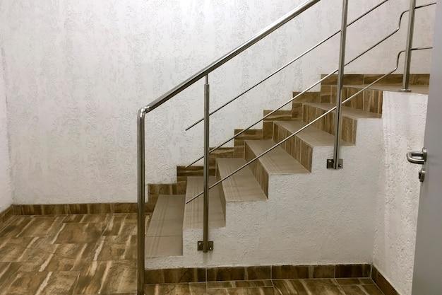 Étapes des escaliers des tuiles à côté du mur plâtré dans un bâtiment moderne industriel. escalier avec mains courantes de style industriel. espace de copie. fermer. à l'intérieur.