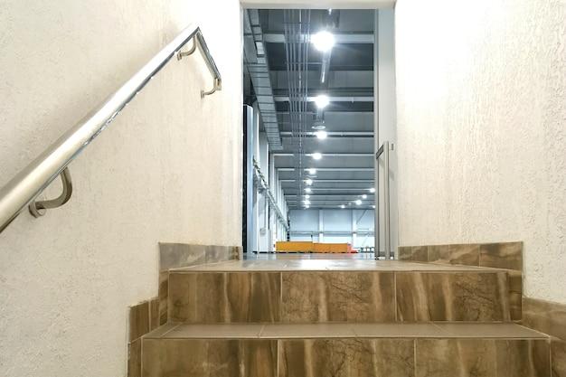 Étapes des escaliers des tuiles à côté du mur plâtré dans la porte ouverte, dans un bâtiment industriel moderne. escalier avec mains courantes de style industriel. espace de copie. fermer. à l'intérieur.