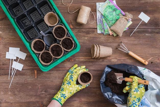 Étapes de la plantation des graines, préparation, mains de femme remplissant les pots organiques avec de la terre