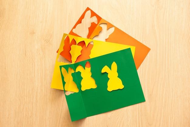 Étapes pour découper les lapins du papier scrapbook de différentes couleurs.