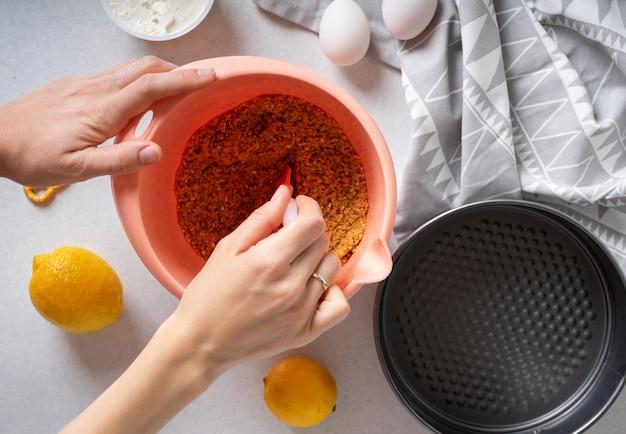 Étapes pour faire une simple tarte au citron avec des craquelins et une garniture à la crème. la main d'une femme mélange des craquelins moulus avec du beurre dans un bol. la base du gâteau.