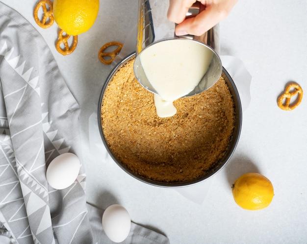 Étapes pour faire une simple tarte au citron avec des craquelins et une garniture à la crème. verser la garniture à la crème sur la base des craquelins à l'aide d'un bol avec un bec verseur.