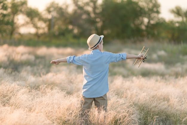 En été, un adolescent avec un modèle réduit d'avion se tient le dos dans les hautes herbes.