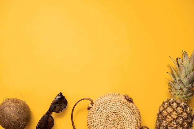 Été coloré tenue de mode féminine plat poser avec sac en bambou et lunettes de soleil