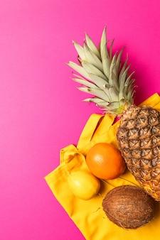 Été, concept de vacances. fruits tropicaux avec un sac en coton jaune sur fond rose