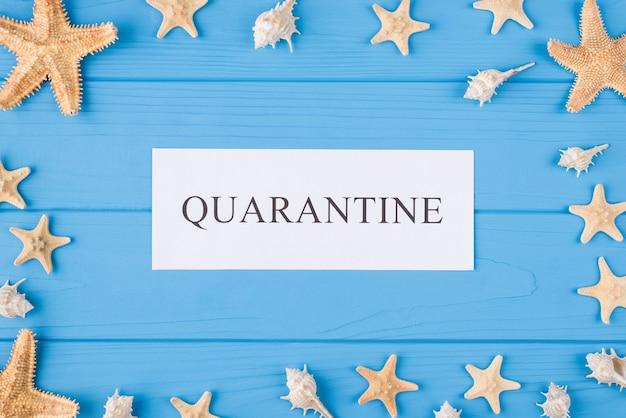 Été dans le concept de quarantaine. en haut au-dessus de la photo vue aérienne du mot de quarantaine et des coquillages et des poissons de mer isolés sur fond de bois bleu