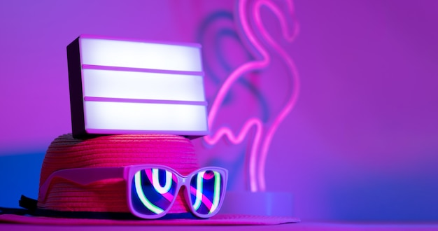 Été avec ligh box vide sur le chapeau avec des lunettes de soleil refection flamingo néon rose et bleu sur la table