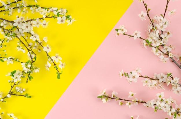 Été plat poser est à venir fond rose et jaune pop avec des branches de fleurs.