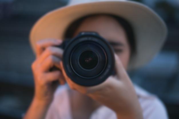 Été souriant portrait lifestyle de joyeuse femme vagabonde s'amusant dans la ville en thaïlande en soirée avec photo de voyage caméra du photographe faire des photos dans un chapeau de style hipster