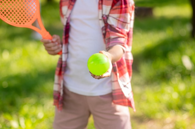 Été, tennis. la main des enfants s'étendant vers l'avant balle de tennis lumineuse à l'extérieur par beau temps, pas de visage