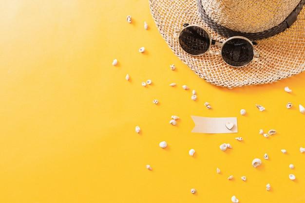 Été voyager à la mer avec chapeau de paille, lunettes de soleil, coquillages sur la vue de dessus de fond jaune