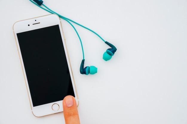 Éteint le téléphone avec le doigt et les écouteurs