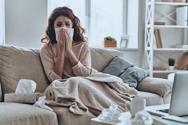 Les éternuements continuent à venir. jeunes femmes malades se mouchant à l'aide de mouchoirs en papier alors qu'elles étaient assises sur le canapé à la maison