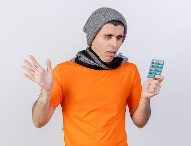 Éternuements jeune homme malade portant chapeau d'hiver avec foulard tenant des pilules et répandre la main isolé sur blanc
