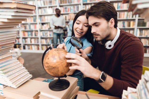 Ethnic asiatique fille et homme blanc utilisent globe.
