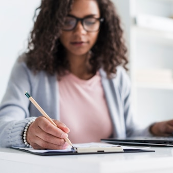 Ethnique jeune femme écrivant sur le presse-papiers