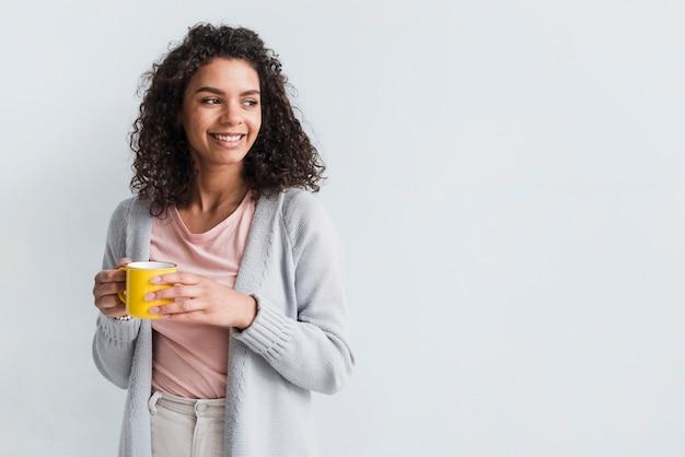 Ethnique jeune femme tenant une tasse sur fond blanc