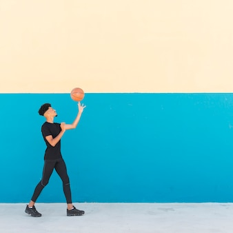 Ethnique mâle spinning basketball sur le doigt