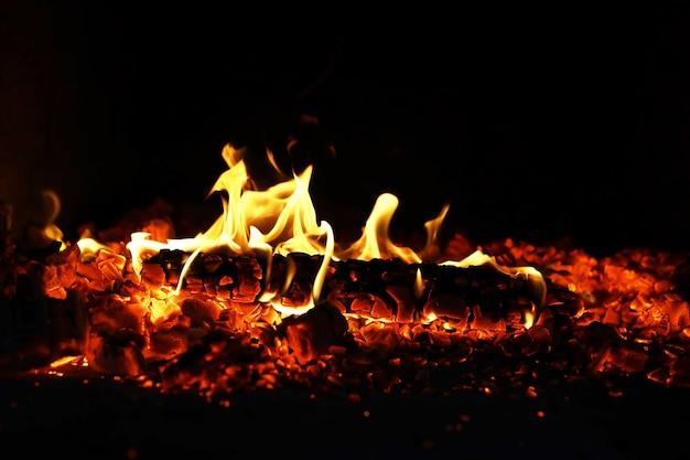 Des étincelles brûlantes rouges volent du grand feu beau fond abstrait sur le thème du feu