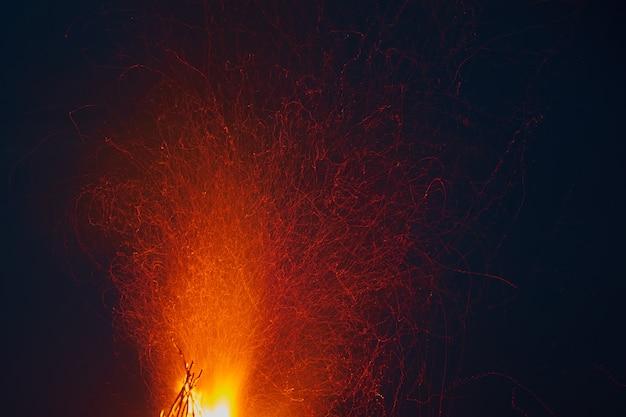 Des étincelles jaillissent du feu sur fond de ciel nocturne.