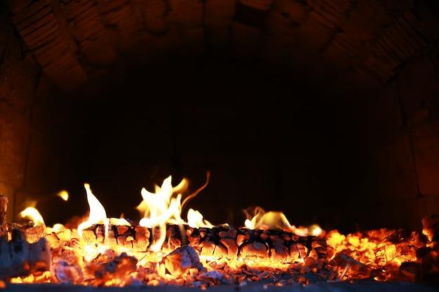 Des étincelles rouges brûlantes volent d'un grand feu. beau fond abstrait sur le thème du feu. des charbons ardents, des particules enflammées s'envolant sur fond noir.