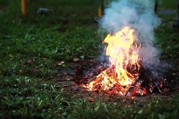 Des étincelles rouges brûlantes volent d'un grand feu. des charbons ardents, des particules enflammées s'envolant sur fond noir.