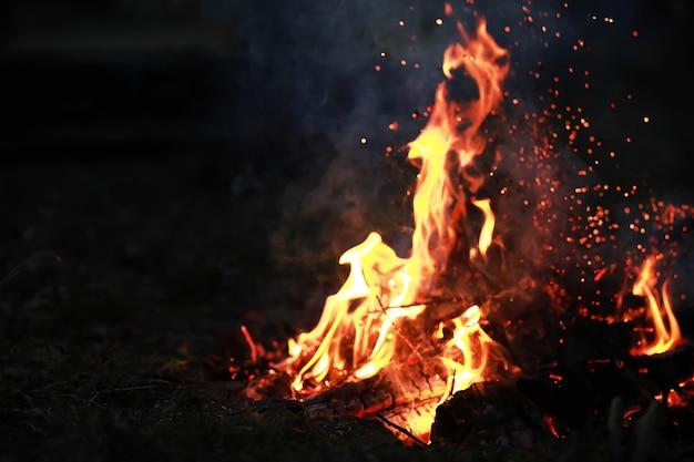 Des étincelles rouges brûlantes volent d'un grand feu des charbons brûlants des particules enflammées s'envolent contre