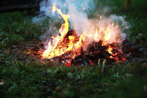 Des étincelles rouges brûlantes volent d'un grand feu des charbons brûlants des particules enflammées s'envolent