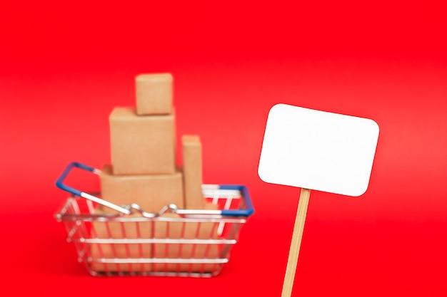 Étiquette blanche se bouchent sur le fond d'un panier avec des boîtes sur fond rouge