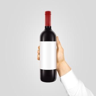Étiquette blanche vierge sur bouteille noire de vin rouge en main isolé