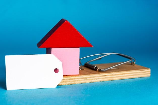 Étiquette blanche vierge et petite maison dans une souricière. assurance immobilière. investissement dans l'immobilier. fraude immobilière résidentielle et commerciale. place pour votre texte. photo de haute qualité